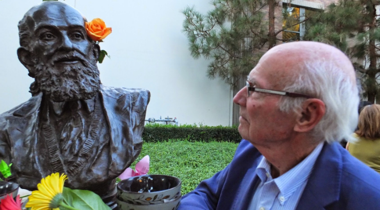 Tom Wilson standing next to Chapman bust of Paulo Freire