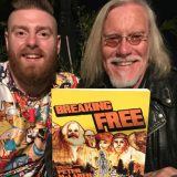 Miles Wilson and Peter McLaren sitting at a table holding their comic book Breaking Free