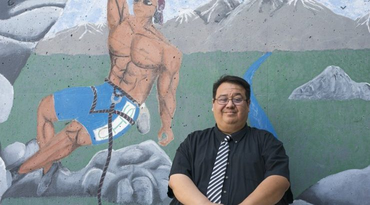 Beau Menchaca in front of mural at Century High School in Santa Ana