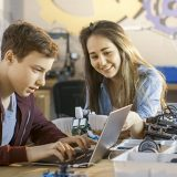 Teacher with student in robotics computer lab
