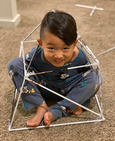 Smiling child sitting inside homemade square geodesic dome