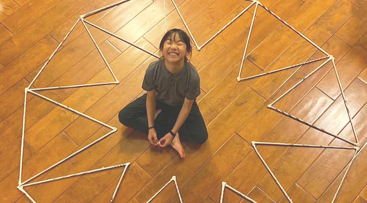 Child on the floor with homemade math structure