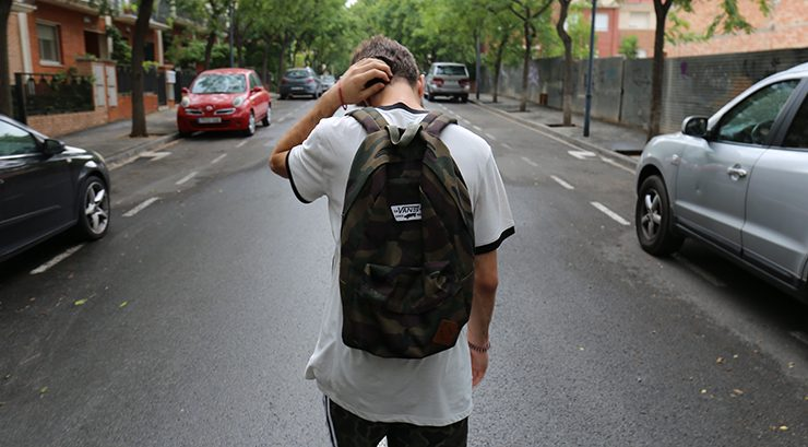 teenage boy walking down a street with back to the camera