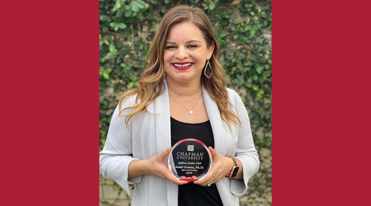 Dr. Audri Sandoval Gomez holding Million Dollar Award
