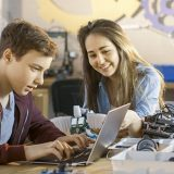 High school student on a laptop with a teacher in a robotics lab