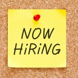 Now Hiring written on a yellow post-it pinned to a cork board
