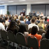 The crowd and panel at the Prop 37 debate.