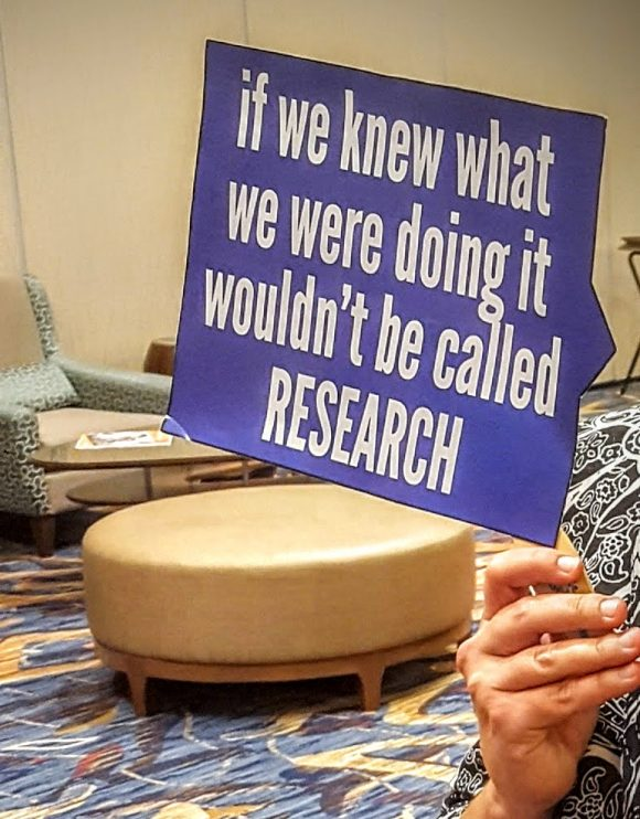 "sign that reads ""if we knew what we were doing it wouldn't be called research."""