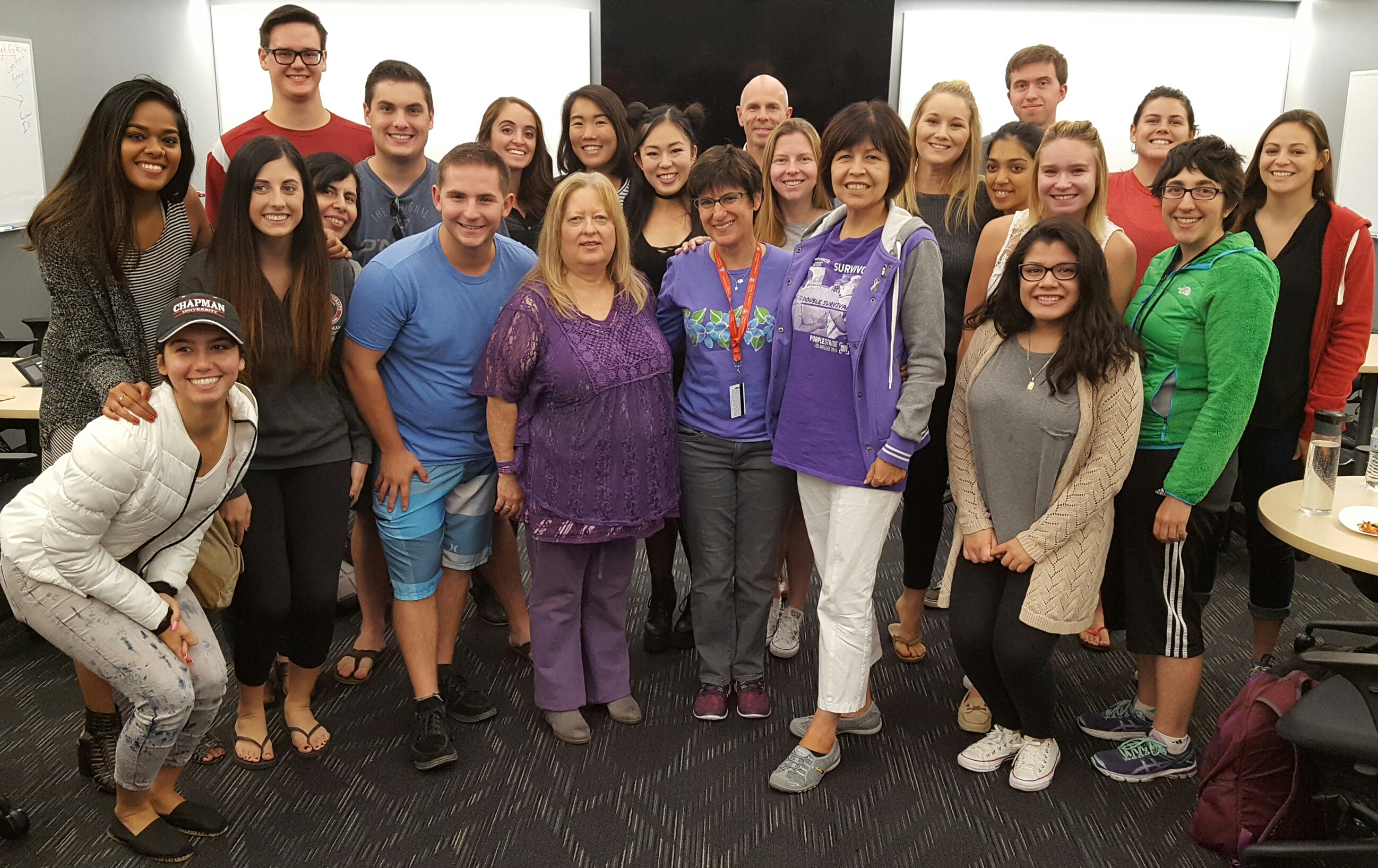 Pancreatic cancer survivors Roberta Luna (front left in purple) and Lupe Romero (front-right in purple) stand with Prof. Melissa Rowland-Goldsmith (front-center in purple) and the students in the Cancer Biology class she co-teaches with Prof. Marco Bisoffi (back center).
