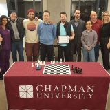 Tournament participants- alumni, students, faculty, and staff- stand with the new champ  Khalid Siddaqi.