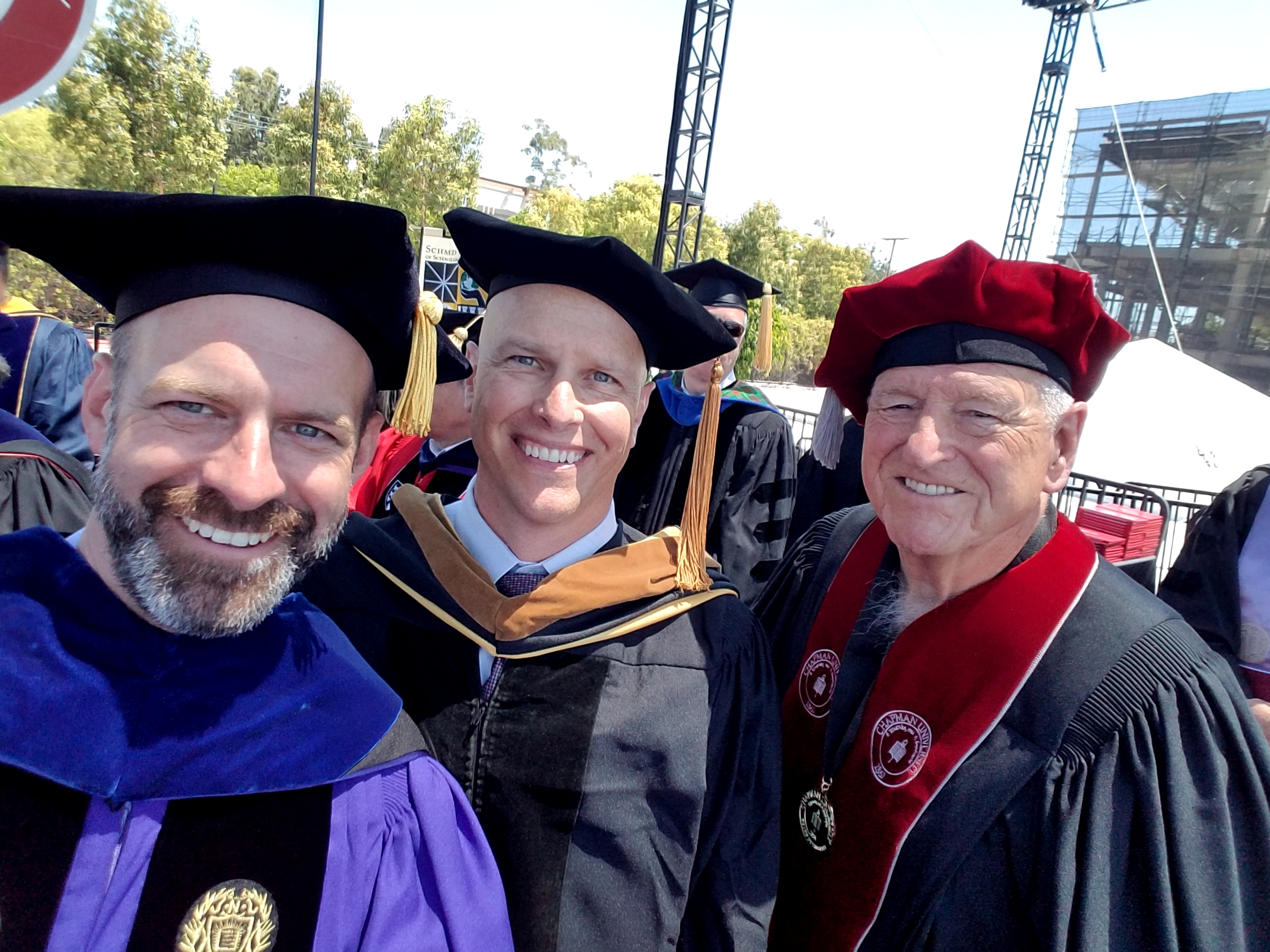Schmid College Dean Andrew Lyon (left) on stage at 2017 Commnecement ceremony with keynote speaker Paul Cook (center) and Trustee Richard Schmid (right)