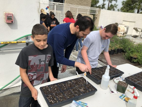 Dr. Atamian shows students how to plant seeds.