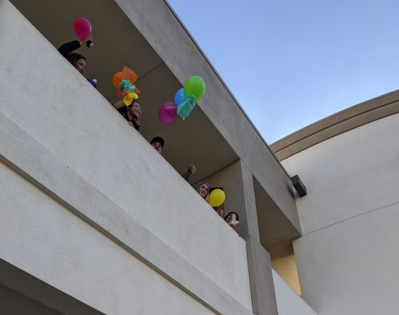 Students throwing eggs in baskets off a second floor