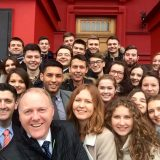 group selfie shot of Law students in front of red building