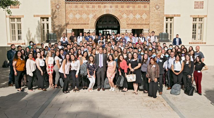A large group of law students posing in front of a law building with arched doorways