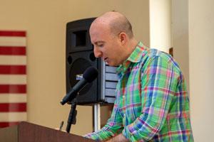 Man in a plaid shirt at a lectern.