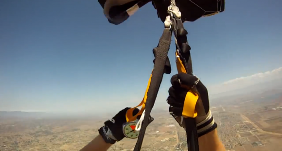 Skydiver's perspective of their hands and the parachute ropes as they descend