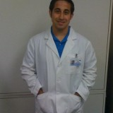 Mike stands wearing a white coat.