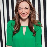 Naomi smiling in a green blouse with a black and white striped background