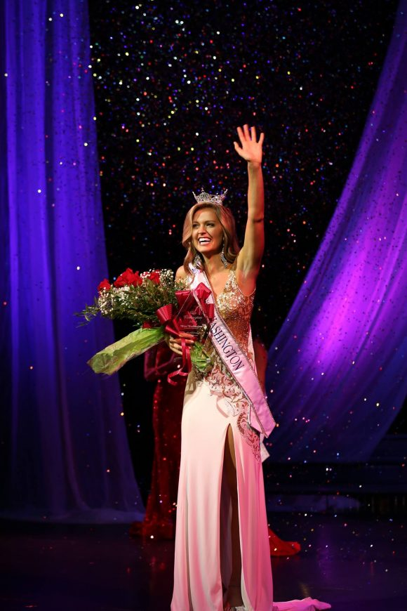 Woman in sparking evening gown waves to crowd with one hand, while clutching a large bouquet of roses with the other.