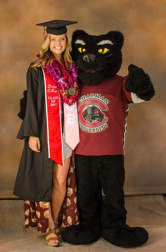 Woman in graduation cap and gown stands next to mascot of a panther.