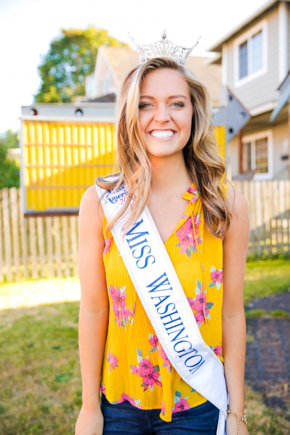 Young woman in her backyard smiles while wearing a tiara and sash from a beauty pageant.