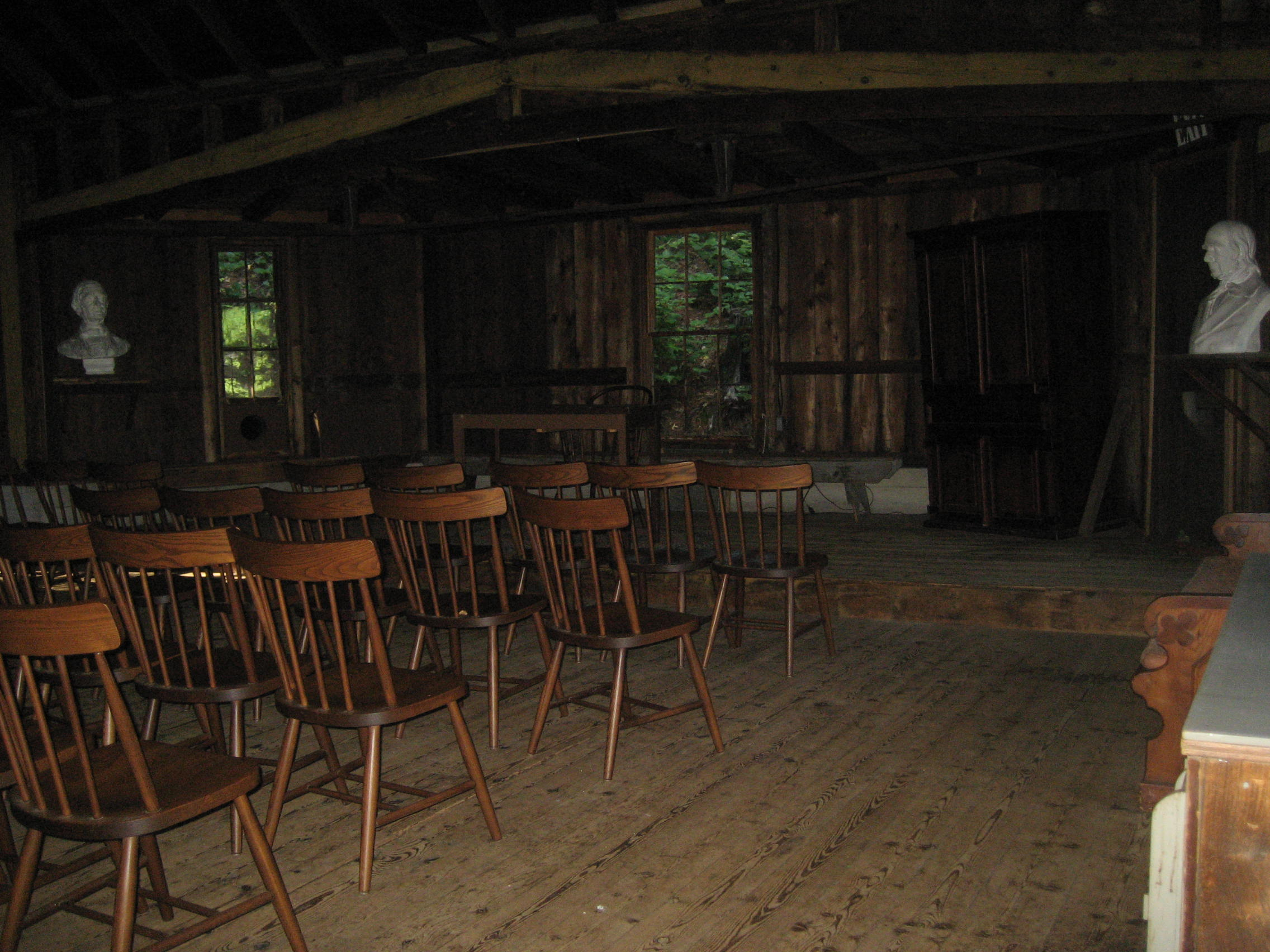 photo of a nineteenth century classrooms with wooden chairs in rows