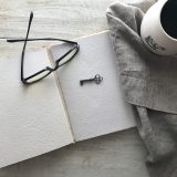 Eyeglasses on a book with a key