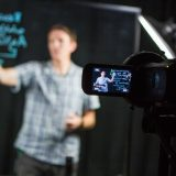 Faculty writing on learning glass in video studio