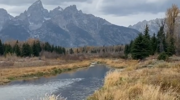 mountains in the distance with a river and brown grass in the foreground