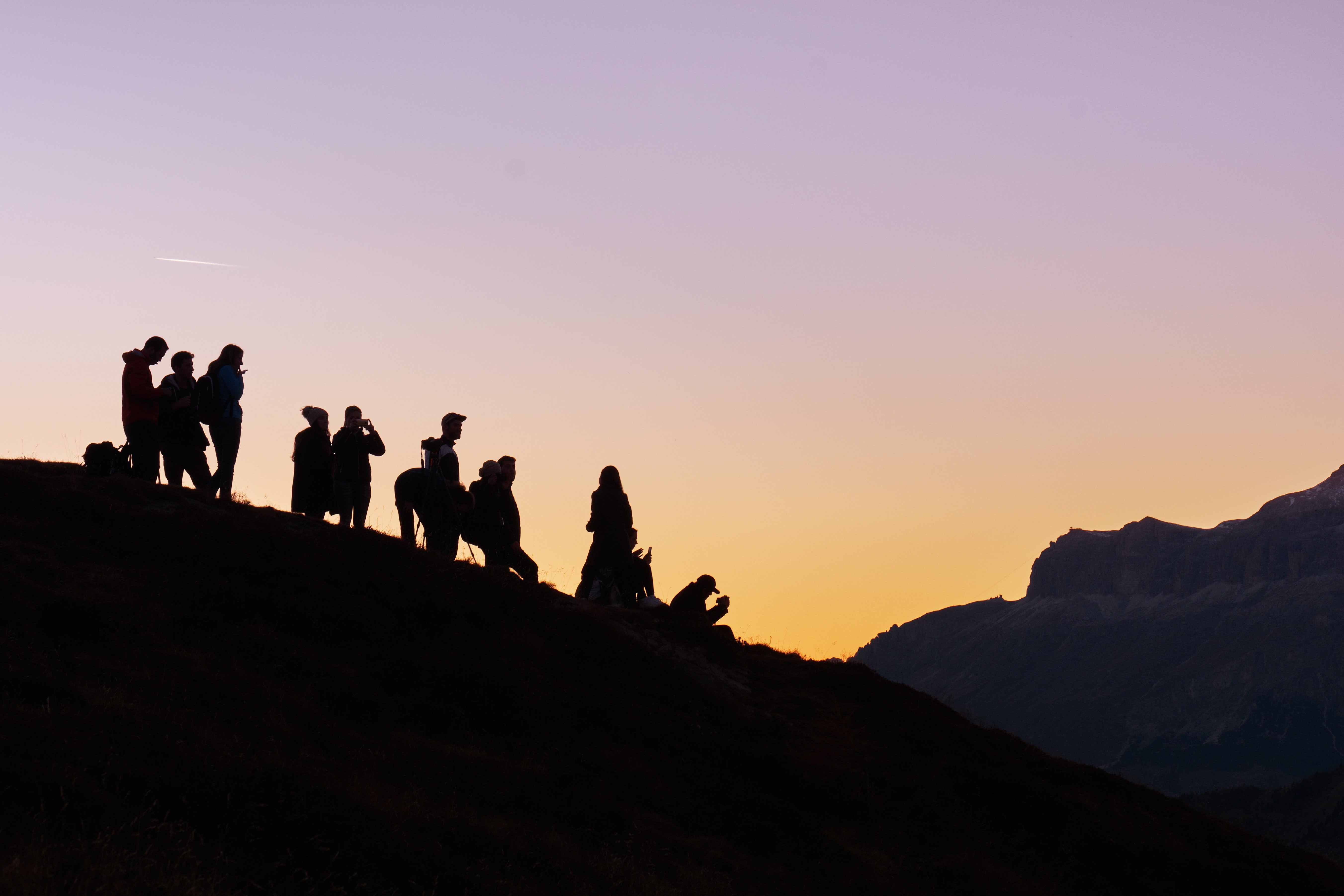 silhouette of hikers on a hill at sunset