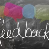 "A chalkboard with the word ""feedback"" and speech bubbles"