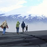 +Students on black sand, mountains