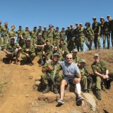 Chapman Trustee David C. Henley, who injured his leg in a fall, is photographed in the Golan Heights with a group of heavily-armed soldiers attached to the Israeli Defense Force's Northern Command.