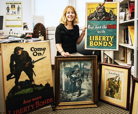 History professor Jennifer Keene displays images from her World War I collection. The object of the propaganda posters is impossible to miss, but the magazine covers and other imagery show that 'Great War' messaging could be quite nuanced and diverse, she says. Photo by Scott Stedman '14.