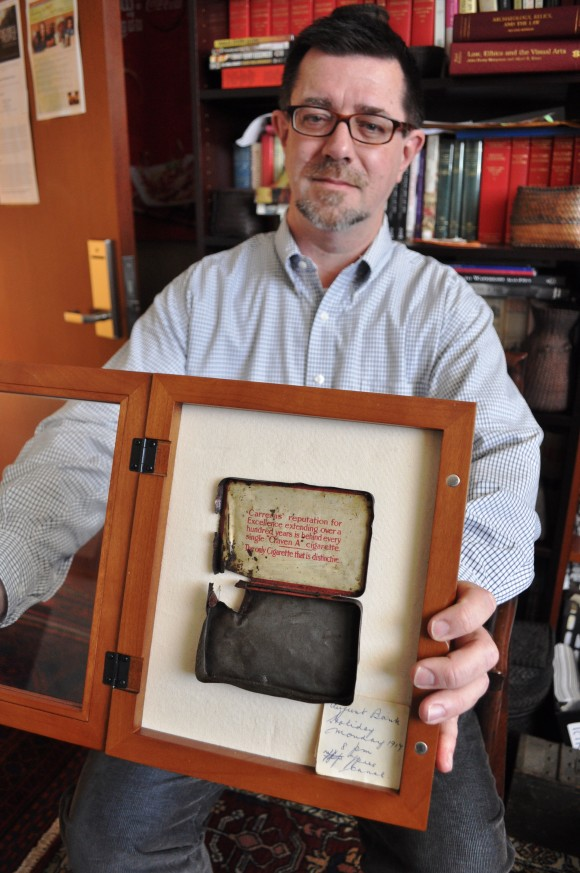"Professor John Hall holds a cigarette tin that was in his grandfather's pocket when the howitzer he and his fellow crew members were operating exploded during one of the battles at Ypres, Belgium. Most of the crew died in the explosion, but Hall's grandfather survived, although he suffered nightmares and ""lingering emotional trauma"" the rest of his life."