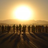 group of people walking into the sunset