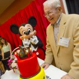 Mickey mouse character and older man in front of cake