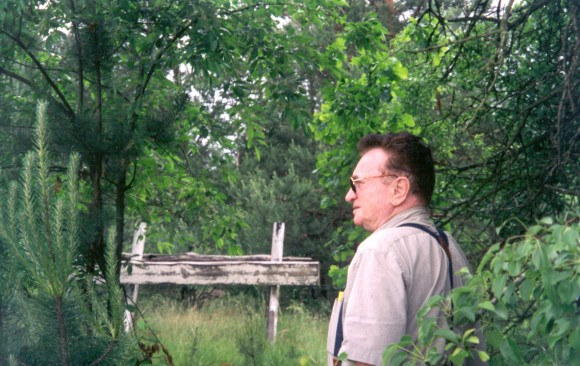Thomas Blatt standing in a field, visiting the end of the tracks at Sobibor