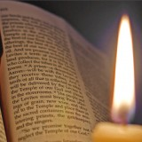 a candle illuminates the pages of the Bibl