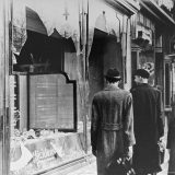 Passersby look at broken front window of store damaged during the events of Kristallnacht.