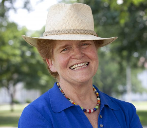 Photo of Deborah Lipstadt wearing a blue blouse, multicolored bead necklace and beige fedora