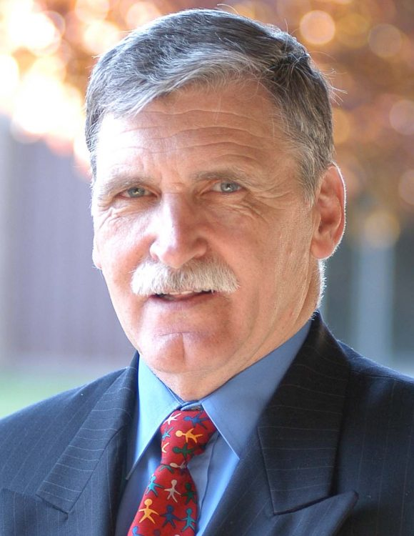 Headshot of Romeo Dallaire wearing a dark suit and red tie with shapes of people of various colors holding hands