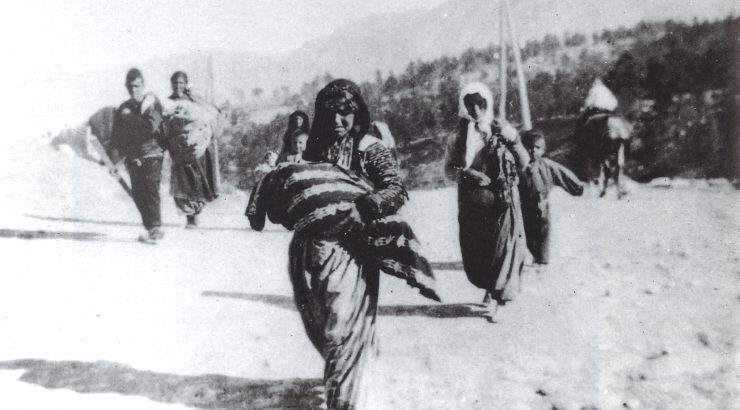 Photo of a woman carrying a bundled child while marching during the Armenian genocide in the Ottoman Empire