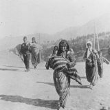 A small group of Armenian deportees walking through the Taurus Mountain region, carrying bundles.