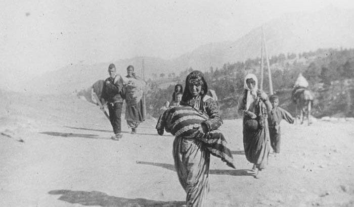A small group of Armenian deportees walking through the Taurus Mountain region, carrying bundles.