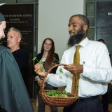 Chaplain handing out a piece of ivy to a graduate