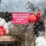 Banner that says Welcome to the Fish Interfaith Center surrounded by black red and white balloons