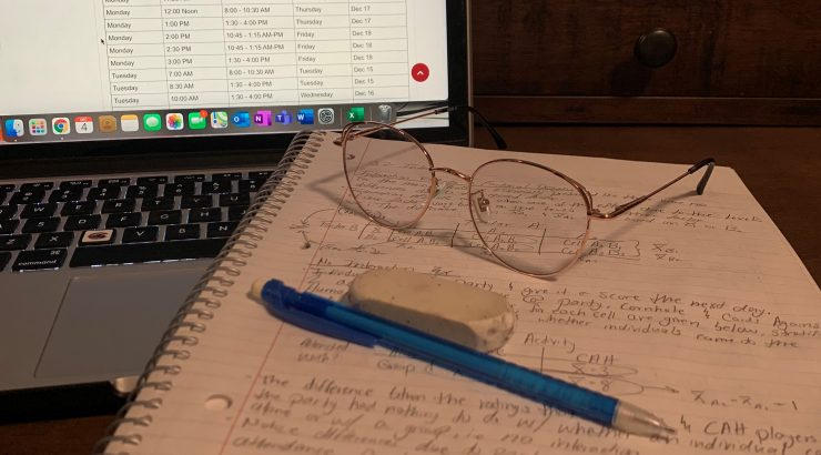 notebook with glasses and a pen in front of a laptop