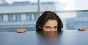 Woman peering over desk